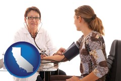 california a female nurse practitioner checking a patient's blood pressure