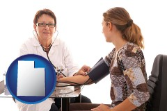 utah a female nurse practitioner checking a patient's blood pressure