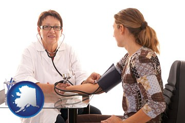a female nurse practitioner checking a patient's blood pressure - with Alaska icon