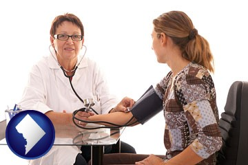 a female nurse practitioner checking a patient's blood pressure - with Washington, DC icon