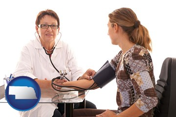 a female nurse practitioner checking a patient's blood pressure - with Nebraska icon