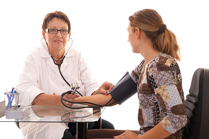 a female nurse practitioner checking a patient's blood pressure